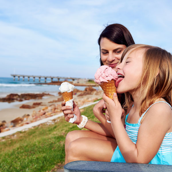 Child and mother eating ice cream by the sea
